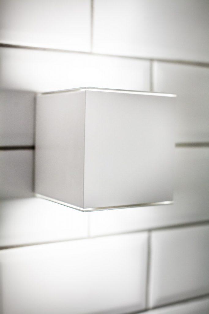 nowoczesny, biały kinkiet o minimalistycznej formie stapiający się z kolorem ściany